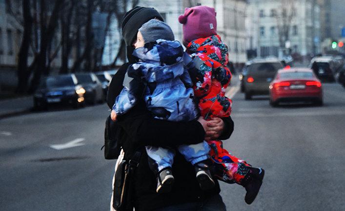 Женщина с двумя детьми на руках переходит дорогу