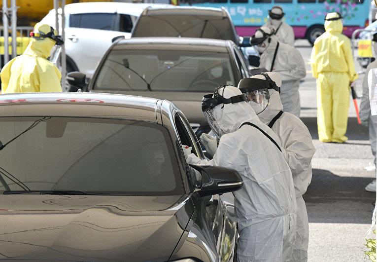 Медицинские работники делают тест на коронавирус в Гояне, Южная Корея