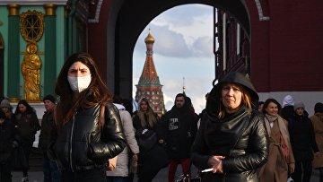 Люди проходят через Воскресенские ворота, ведущие на Красную площадь, в Москве