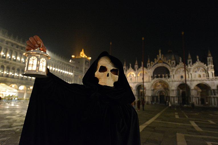 Человек в костюме Смерти на пустой Площади святого Марка в Венеции, Италия