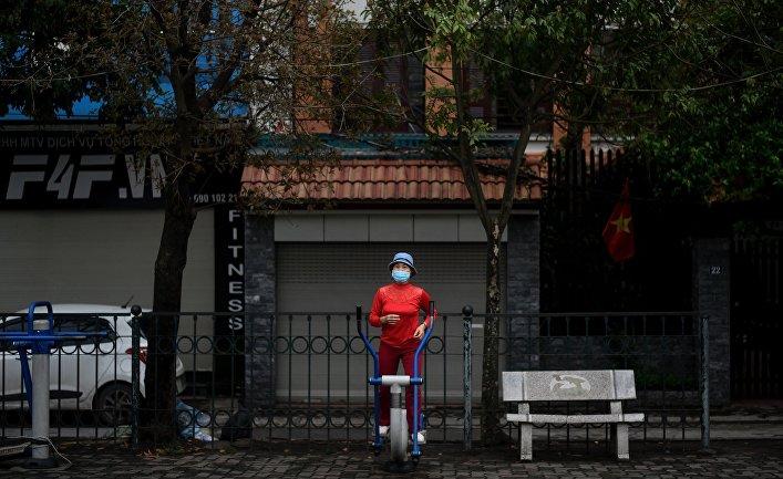 Человек занимается фитнесом, не снимая маски. Ханой, Вьетнам