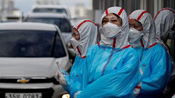 Медицинский персонал в защитном снаряжении в медицинском центре Университета Юннам в Тэгу, Южная Корея