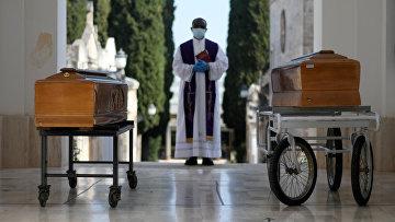 Священник и два гроба с жертвами коронавируса, Италия