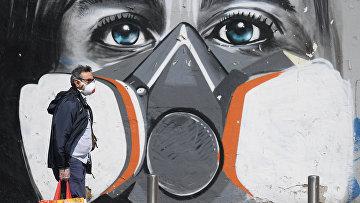 Мужчина в маске идет мимо граффити в Милане, Италия