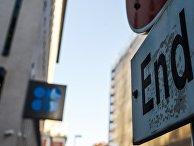 """Надпись """"Конец"""" на дорожном знаке перед зданием Организации стран - экспортеров нефти в Вене"""