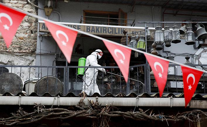 Рабочий распыляет дезинфицирующее средство на Гранд-Базаре в Стамбуле, Турция