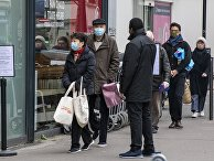 Люди стоят в очереди возле продуктового магазина в Париже
