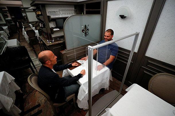 Владельцы ресторана проверяют защитные экраны в своем ресторане в Риме
