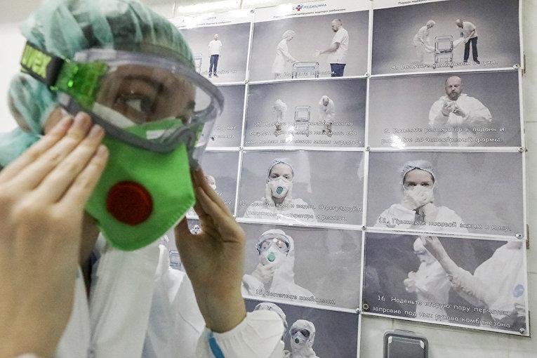 Медицинский работник надевает защитный костюм рядом с инструкцией в ЦКБ «РЖД-Медицина» в Москве