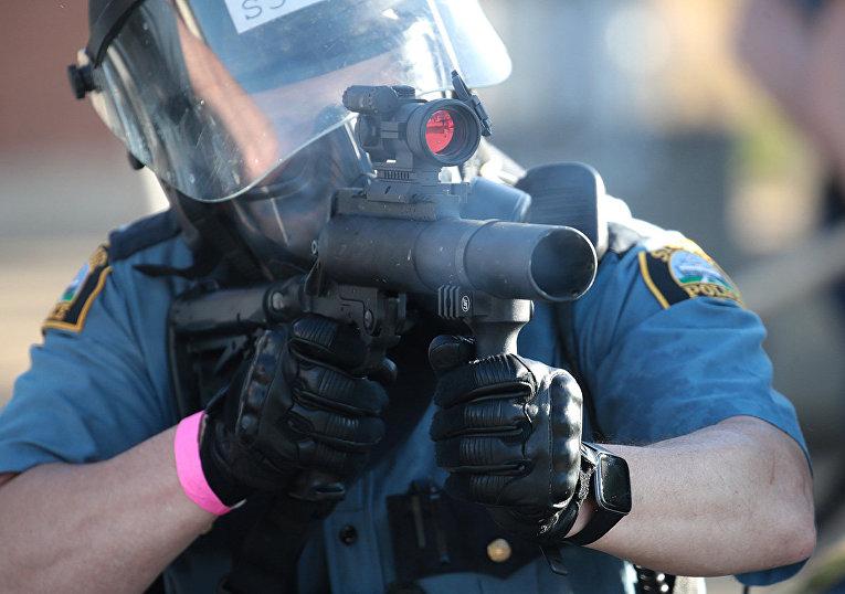 Сотрудник полиции стреляет слезоточивым газом в протестующих в Сент-Поле, штат Миннесота