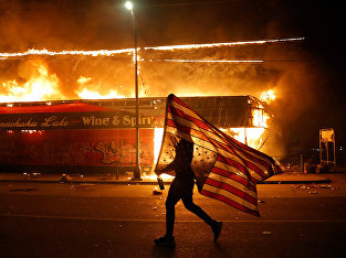 Протестующий с перевернутым флагом США в Миннеаполисе
