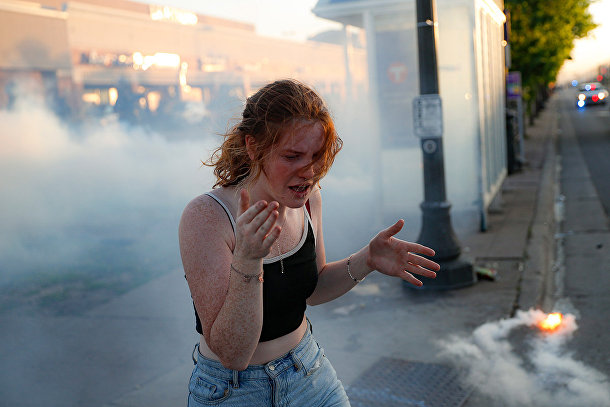 Участница протестов в облаке слезоточивого газа в Сент-Поле, штат Миннесота