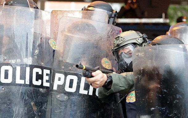 Полицейский стреляет резиновыми пулями в протестующих в Майами
