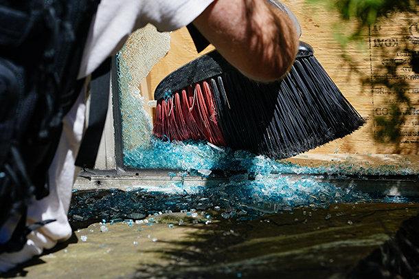 Мужчина убирает осколки стекла в пострадавшем от беспорядков магазине в Атланте