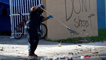 Мужчина убирает улицу рядом в граффити «Не стреляйте» в Майами