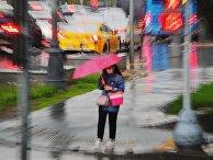 Девушка под зонтом у пешеходного перехода ждет переключения светофора на зеленый свет во время дождя, Москва