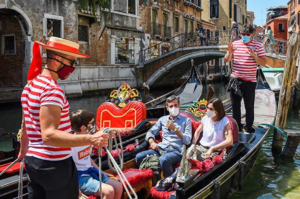 Туристы катаются на гондоле по каналам Венеции