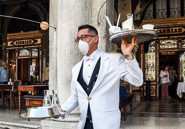 Официант обслуживает клиентов на террасе кафе «Флориан»