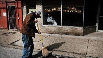 Безработный подметает улицу за вознаграждение в городе Клэртон, штат Пенсильвания