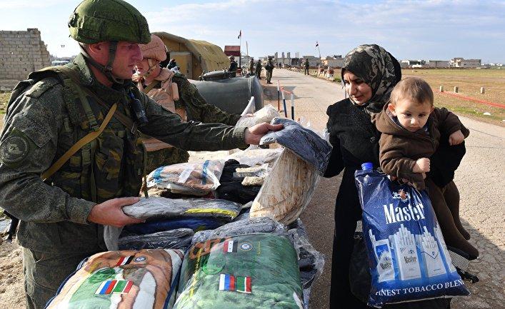 Военнослужащие российского центра по примирению враждующих сторон раздают гуманитарную помощь сирийским беженцам на территории гуманитарного коридора Абу-Духур в окрестностях провинции Идлиб