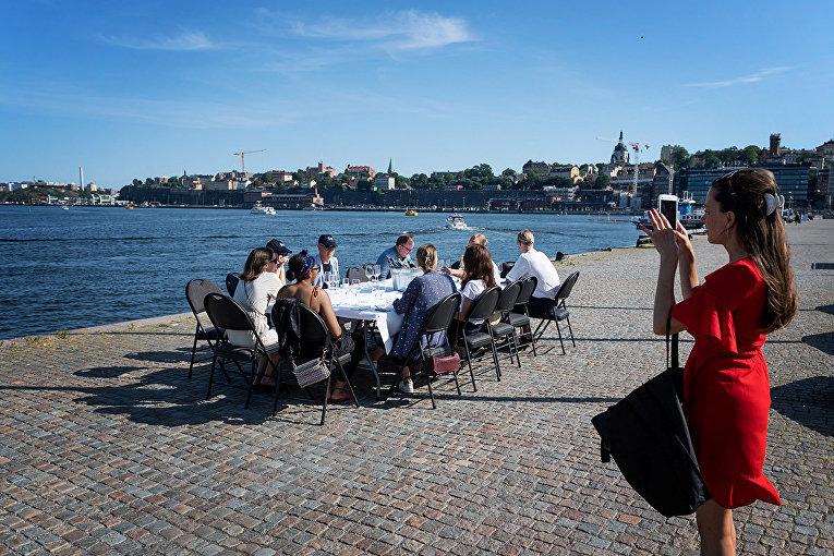 Отдыхающие за столом на набережной в Стокгольме