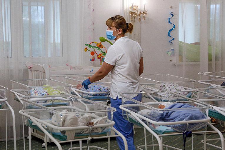 Медсестра в заботится о младенцах, рожденных суррогатными матерями в Киеве