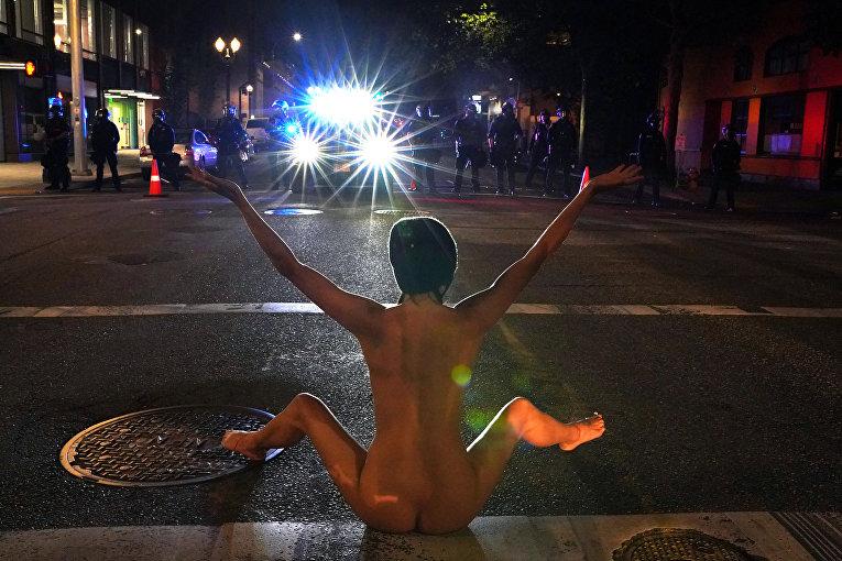 Обнаженная женщина занимается йогой перед полицейскими в знак протеста против расового неравноправия, Портленд, США