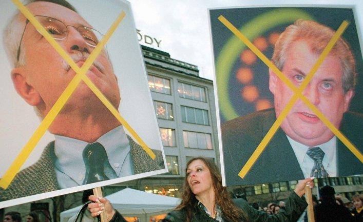 Женщина держит плакат портретами Вацлава Клауса и Милоша Земана во время митинга на Вацлавской площади в Праге