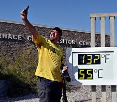 Турист делает селфи с термометром в Долине Смерти