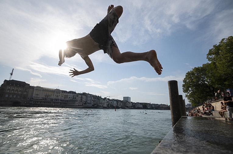 Юноша ныряет в реку Рейн в Базеле, Швейцария