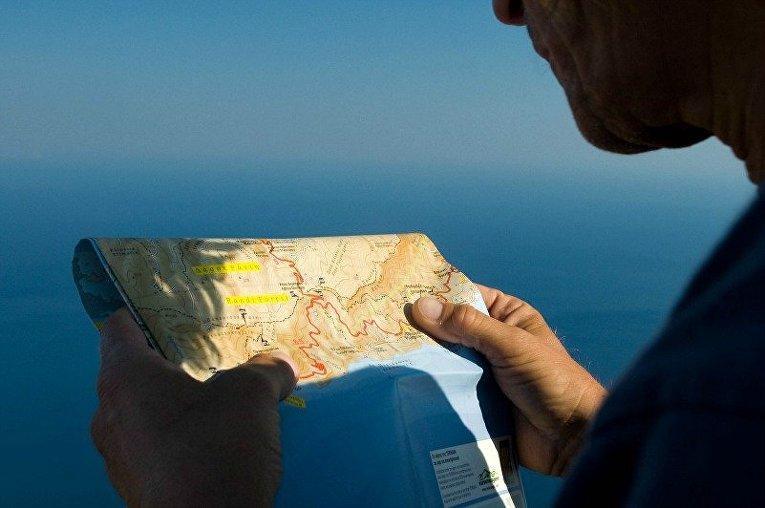 Турист с картой греческого острова Икария
