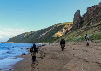 Участники экспедиции идут по берегу бухты Тетяева острова Уруп (остров южной группы Большой гряды Курильских островов).