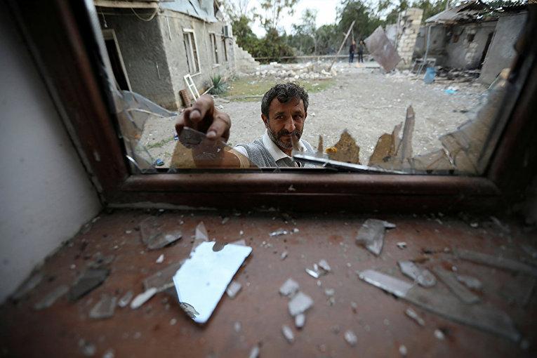 Мужчина убирает битое стекло после обстрела в селе Гарагоюнлу, Азербайджан