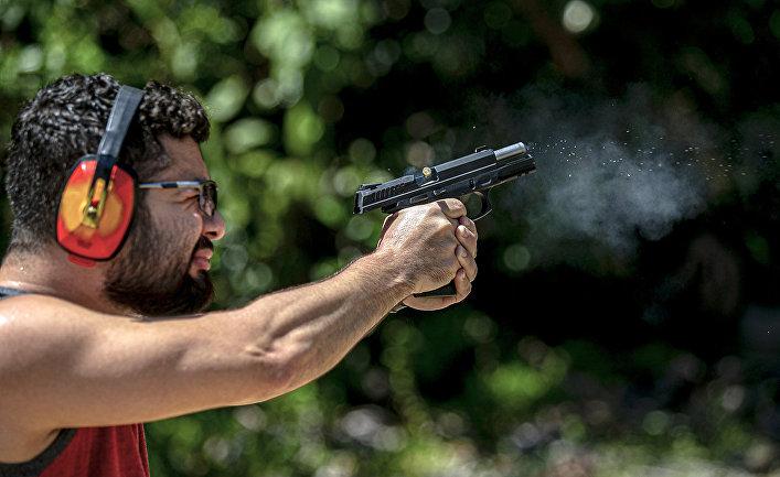 Мужчина стреляет из пистолета в стрелковом клубе в Белеме, Бразилия