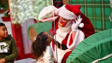 Дети общаются с Санта-Клаусом, сидящим за защитным стеклом