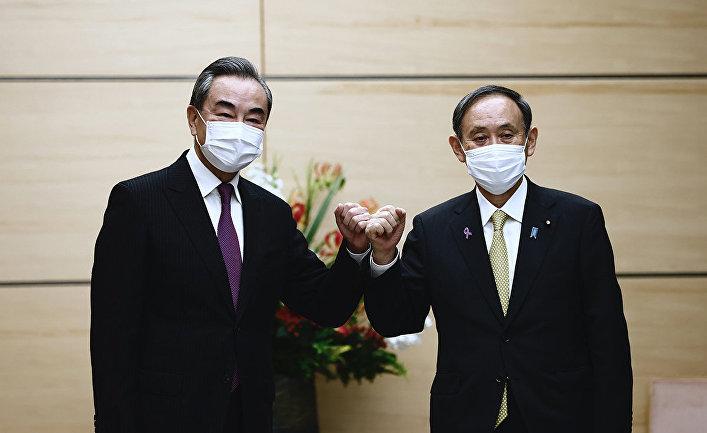 Премьер-министр Японии Ёсихидэ Суга и министр иностранных дел Китая Ван И на встречи в Токио