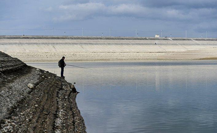 Мужчина ловит рыбу на берегу Аянского водохранилища в Крыму