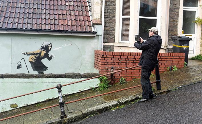Мужчина фотографирует новую работу Бэнкси «Апчхи», Бристоль, Великобритания