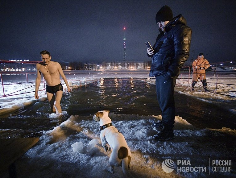 Мужчина выходит из крещенской купели на реке Волхов в Великом Новгороде