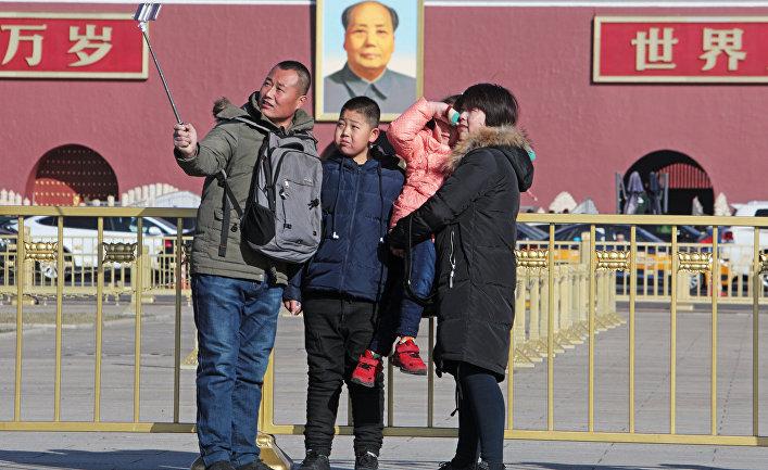 Семья фотографируется у портрета Мао Цзэдуна на центральной площади Пекина - Тяньаньмэнь