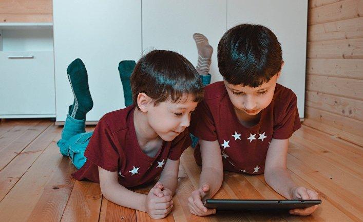 Дети играют в игру на планшетном компьютере