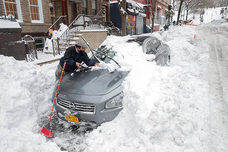 Мужчина очищает автомобиль от снега в Нью-Йорке
