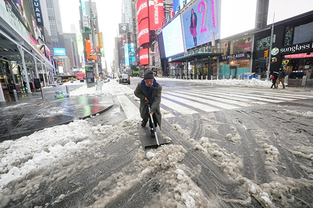 Мужчина убирает снег на Таймс-сквер в Нью-Йорке