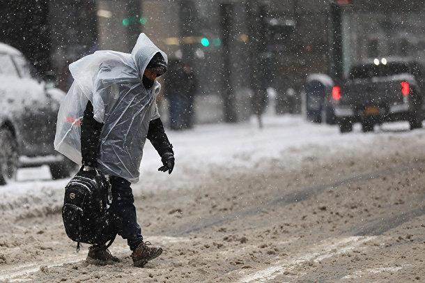 Прохожий во время снегопада в Нью-Йорке