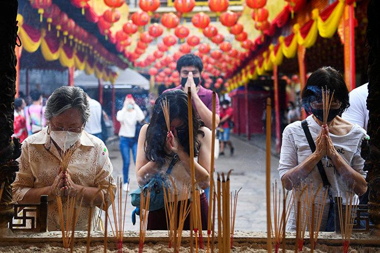Люди молятся в храме в преддверии Лунного Нового года в Бангкоке, Таиланд