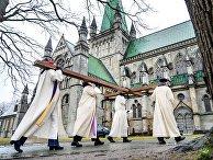 Священнослужители несут крест в католический собор в Тронхейме, Норвегия, в Страстную пятницу