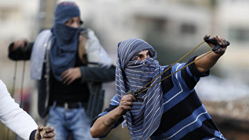 Палестинцы кидают камни во время столкновений с израильскими солдатами