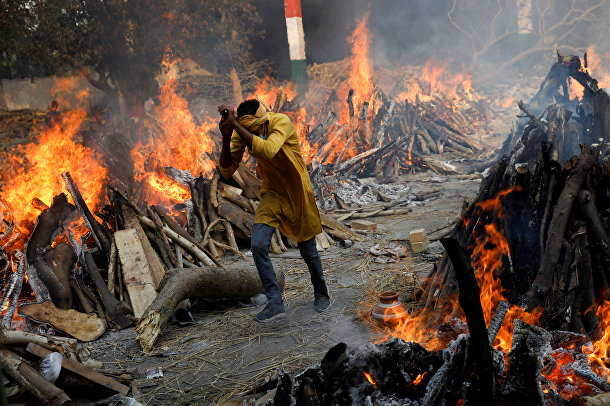 Мужчина среди рядов погребальных костров в крематории в Нью-Дели, Индия, где сжигают скончавшихся от covid-19