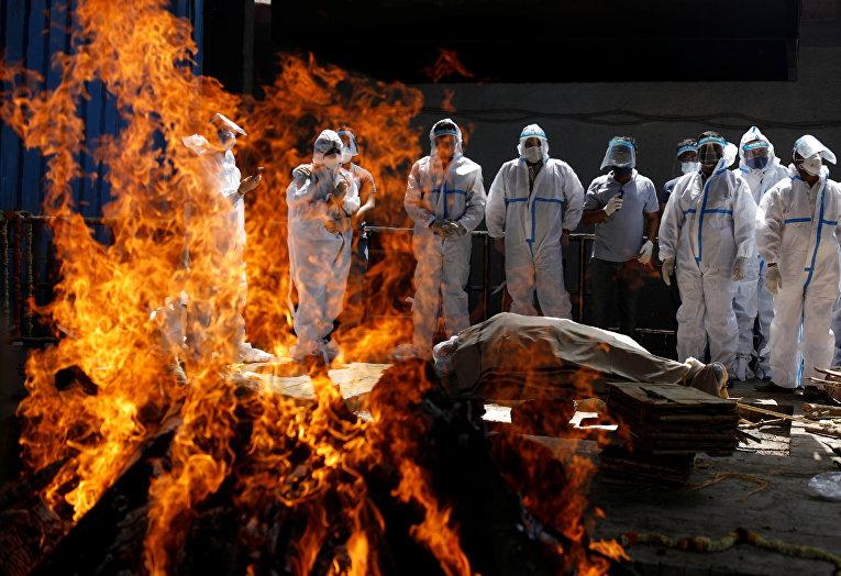 Родственники в защитных костюмах на похоронах скончавшегося от covid-19 в Нью-Дели, Индия