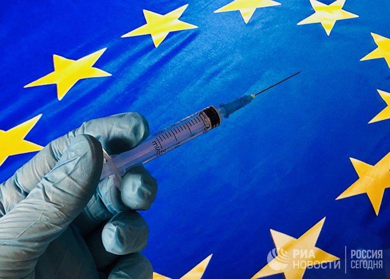 Медицинский шприц на фоне флага ЕС